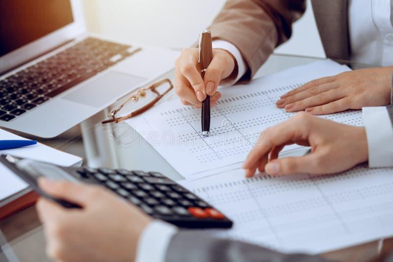 Dos contables de sexo femenino que cuentan en la renta de la calculadora para el primer de las manos de la realizaci?n de la form imagenes de archivo