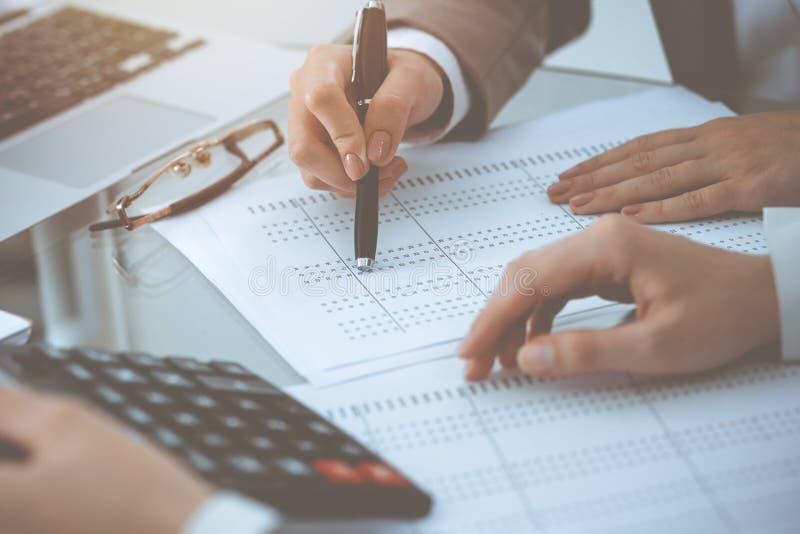 Dos contables de sexo femenino que cuentan en la renta de la calculadora para el primer de las manos de la realizaci?n de la form foto de archivo