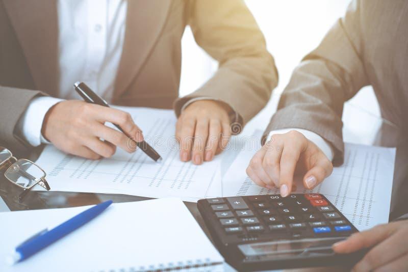 Dos contables de sexo femenino que cuentan en la renta de la calculadora para el primer de las manos de la realizaci?n de la form fotos de archivo
