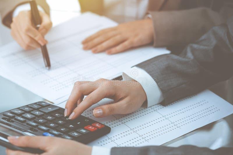 Dos contables de sexo femenino que cuentan en la renta de la calculadora para el primer de las manos de la realizaci?n de la form imágenes de archivo libres de regalías