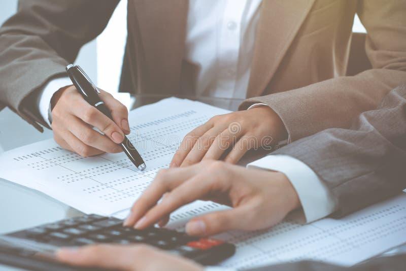 Dos contables de sexo femenino que cuentan en la renta de la calculadora para el primer de las manos de la realizaci?n de la form foto de archivo libre de regalías