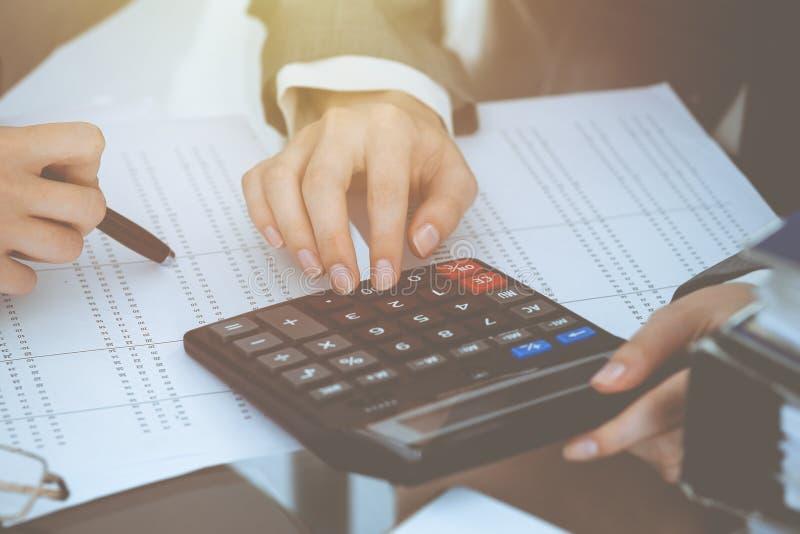 Dos contables de sexo femenino que cuentan en la renta de la calculadora para el primer de las manos de la realizaci?n de la form fotografía de archivo