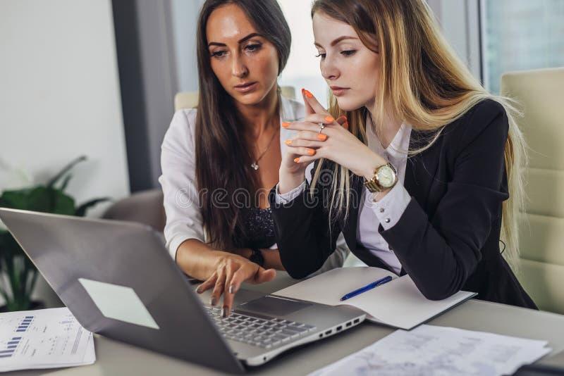 Dos contables de sexo femenino que trabajan junto en informe financiero usando el ordenador portátil que se sienta en el escritor foto de archivo libre de regalías