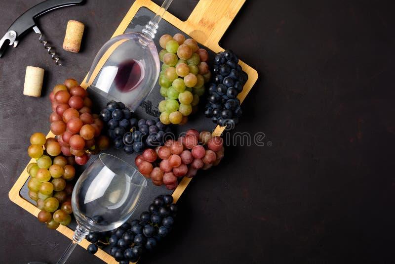 Dos copas con el vino blanco rojo y, las uvas, el sacacorchos y los corchos mintiendo en fondo de madera oscuro fotos de archivo libres de regalías