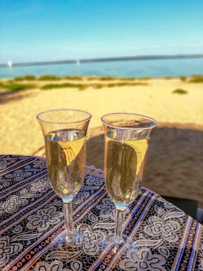 Dos copas de champán en la mesa cerca del océano fotografía de archivo libre de regalías