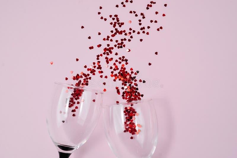 Dos copas de vino que tintineaban vertieron confeti rojo del coraz?n en fondo rosado del papel del color Estilo m?nimo foto de archivo