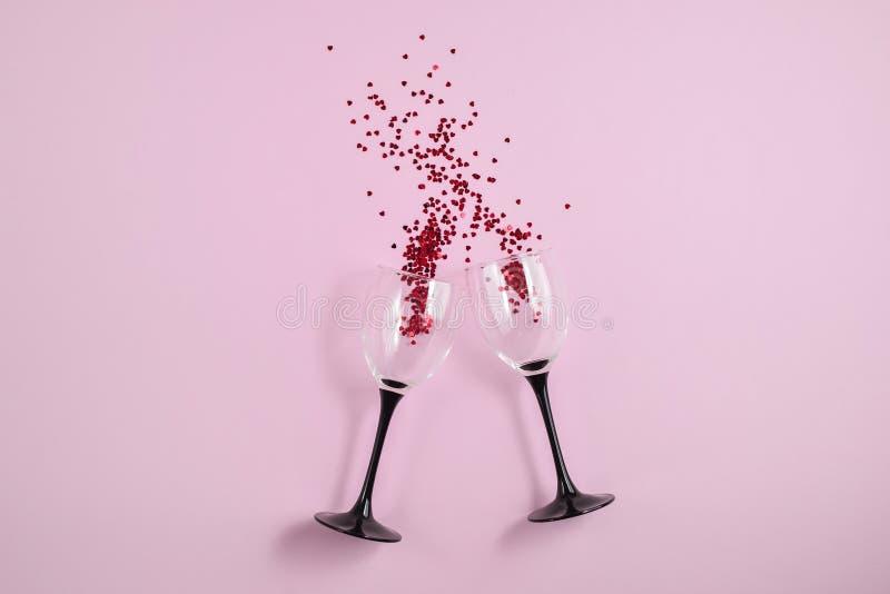 Dos copas de vino que tintineaban vertieron confeti rojo del coraz?n en fondo rosado del papel del color Estilo m?nimo fotos de archivo libres de regalías