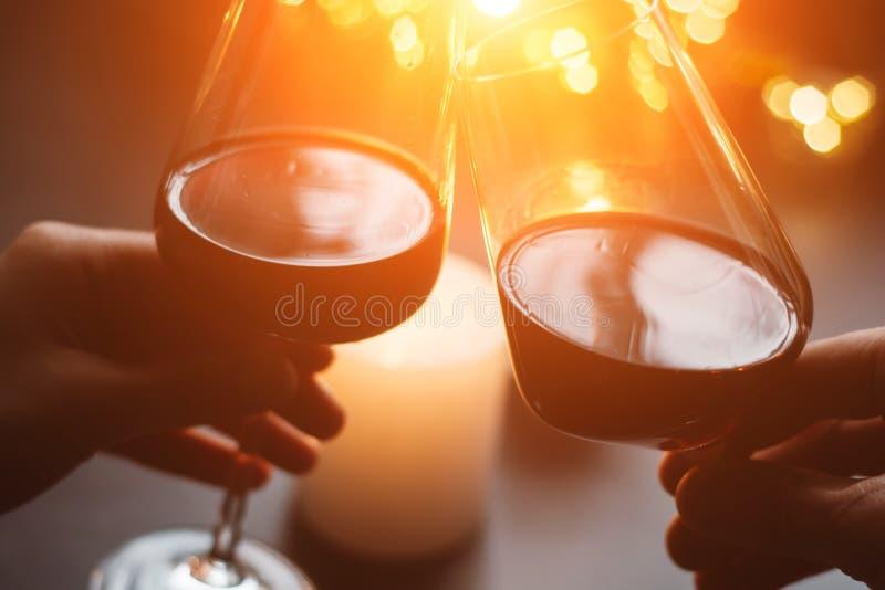 Dos copas de vino rojas a disposición en la vela y las guirnaldas del fondo fotos de archivo