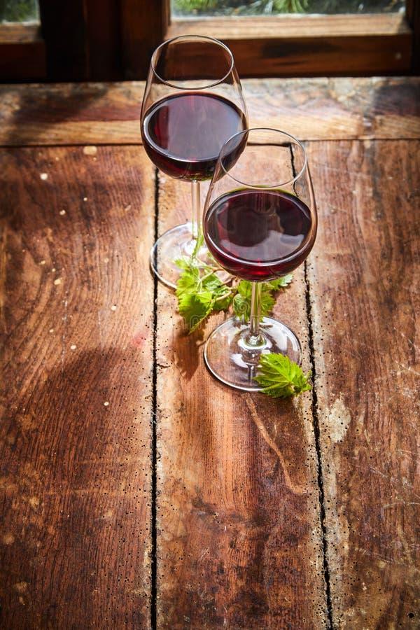 Dos copas de vino tinto con hojas de vid foto de archivo libre de regalías