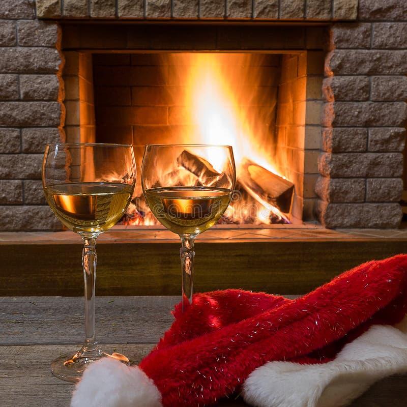 Dos copas de vino y sombreros blancos de Santa Claus de la Navidad contra firepace acogedor fotografía de archivo