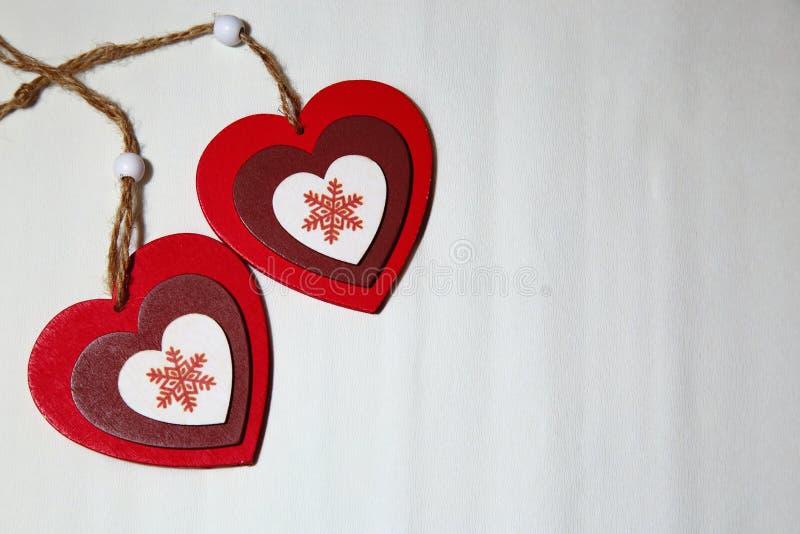 Dos corazones brillantes hermosos con los copos de nieve en un backgroun blanco imagenes de archivo