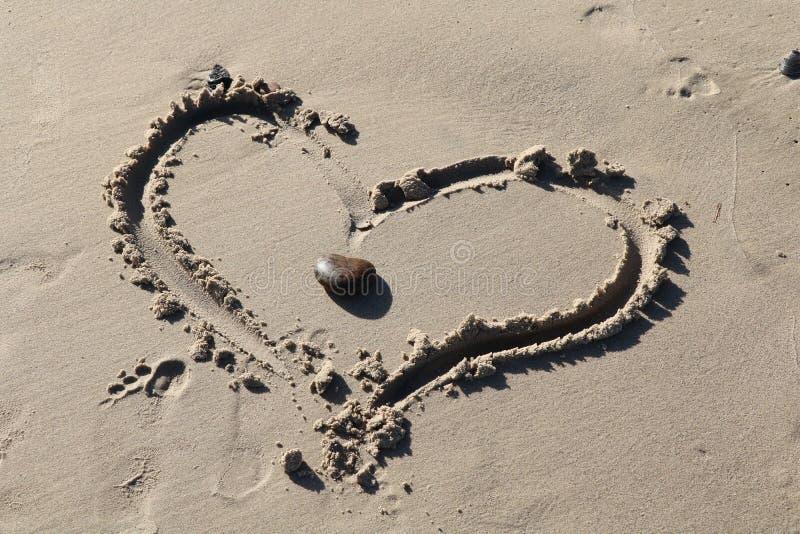 Dos corazones como uno en una playa foto de archivo
