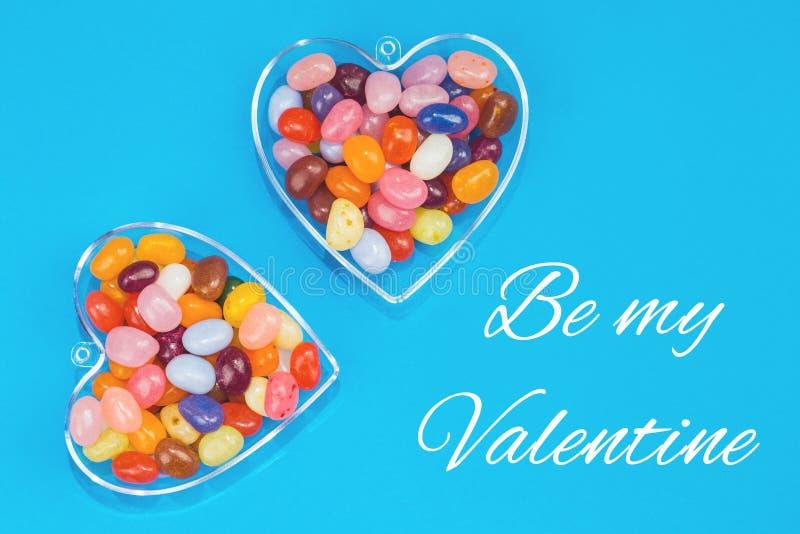 Dos corazones con los caramelos en fondo azul imagen de archivo