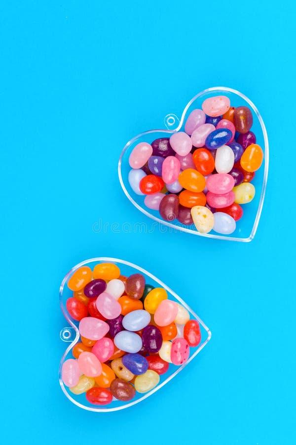 Dos corazones con los caramelos en fondo azul fotografía de archivo