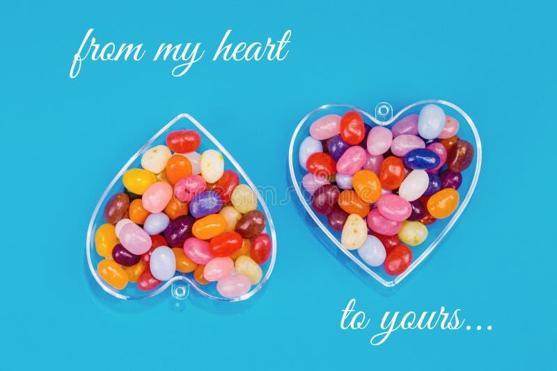 Dos corazones con los caramelos en fondo azul imagenes de archivo