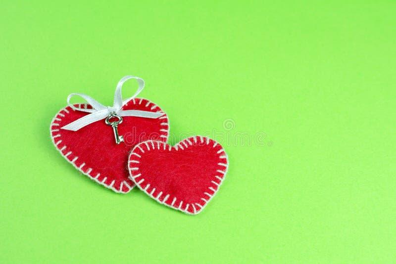 Dos corazones decorativos hechos del fumirana rojo cosido con un hilo blanco foto de archivo libre de regalías