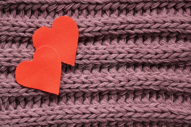 Dos corazones del algodón en un fondo violeta hecho punto fotos de archivo