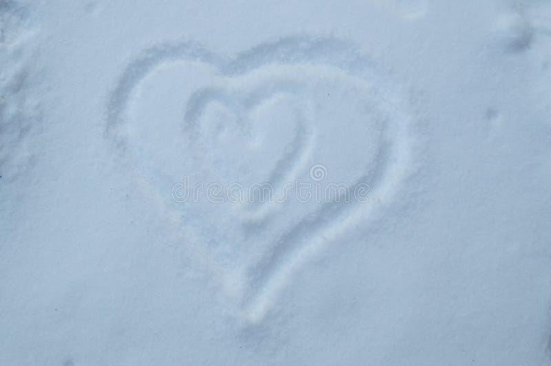 Dos corazones dibujados en nieve, símbolo del embarazo, amor foto de archivo