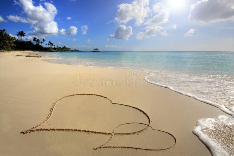 Dos corazones en la arena foto de archivo