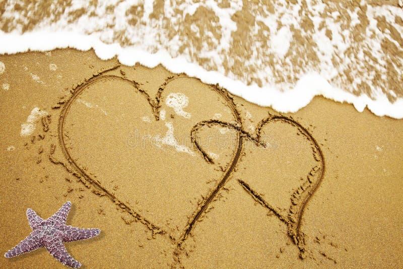Dos corazones en una arena fotos de archivo