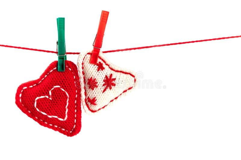 Dos corazones hechos punto en una cadena roja foto de archivo