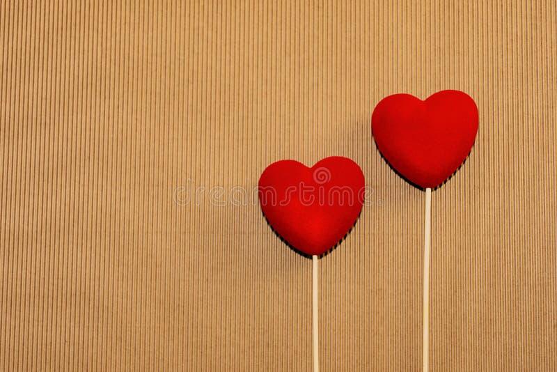 Dos corazones rojos del terciopelo en una superficie marrón natural del cartón Postal de los saludos del día de tarjeta del día d ilustración del vector