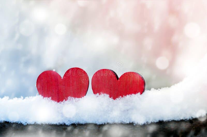 Dos corazones rojos del vintage romántico hermoso junto en un fondo blanco del invierno de la nieve Amor y concepto del día de ta fotografía de archivo libre de regalías