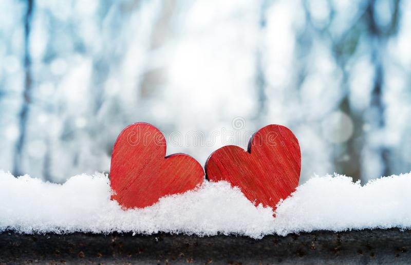 Dos corazones rojos del vintage romántico hermoso junto en un fondo blanco del invierno de la nieve Amor y concepto del día de ta imágenes de archivo libres de regalías