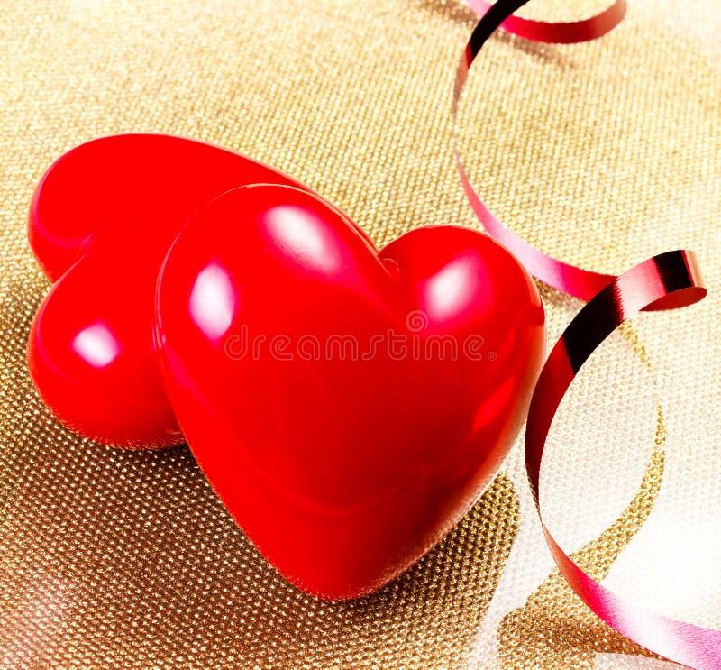 Dos corazones rojos en cierre de oro de la placa para arriba. Backgrou del día de tarjetas del día de San Valentín fotografía de archivo