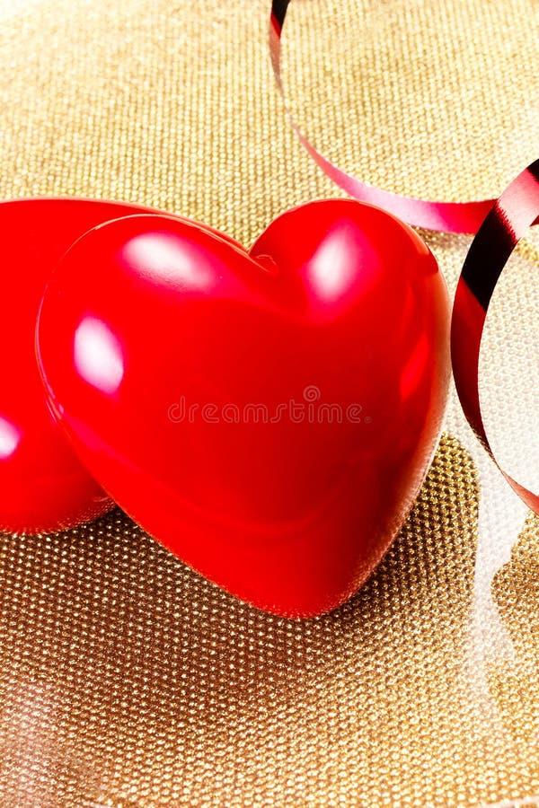 Dos corazones rojos en cierre de oro de la placa para arriba. Backgrou del día de tarjetas del día de San Valentín imágenes de archivo libres de regalías