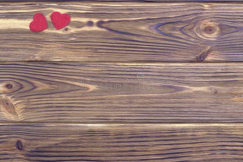 Dos corazones rojos en fondo de madera marrón fotos de archivo