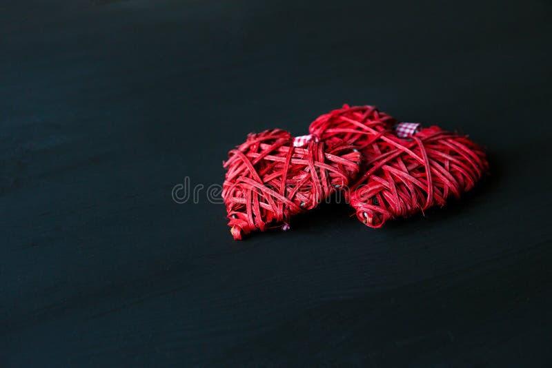 Dos corazones rojos en la tabla de madera negra Tarjetas del día de San Valentín, fondo de la primavera Mofa para arriba con el c imagen de archivo libre de regalías