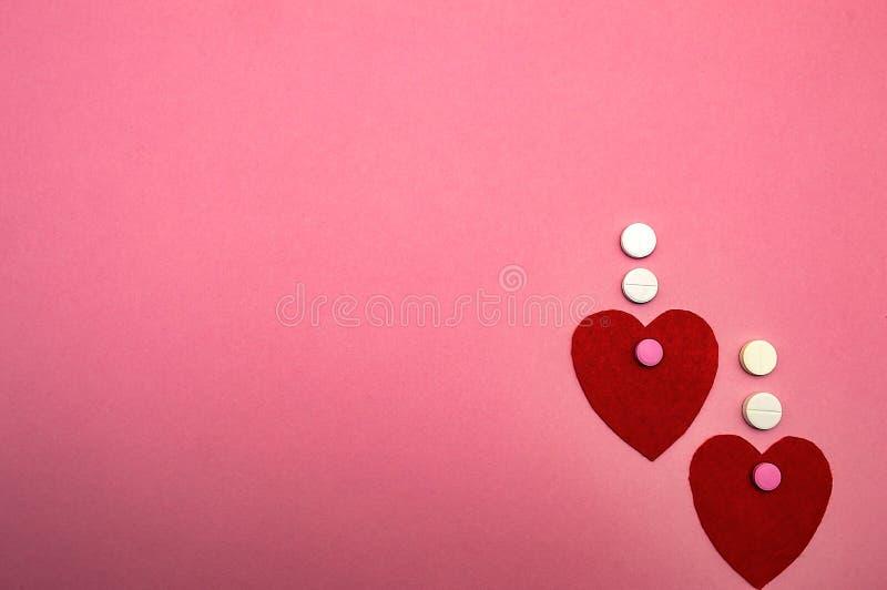 Dos corazones rojos en un fondo rosado con amor de la medicina de las píldoras imagen de archivo