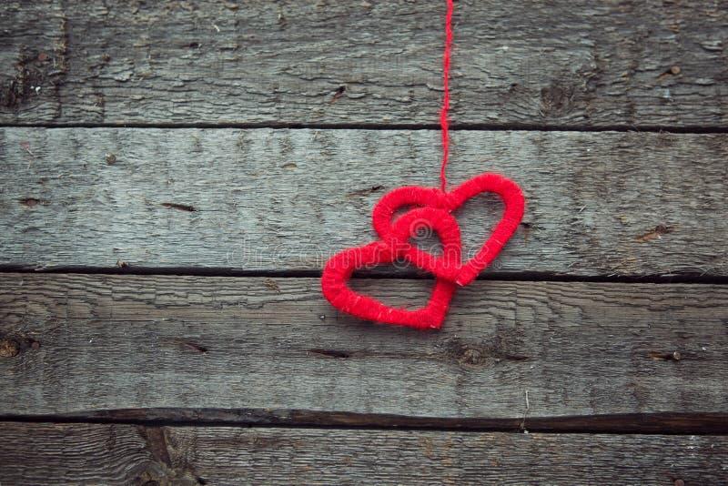Dos corazones rojos en viejo fondo de madera lamentable fotografía de archivo