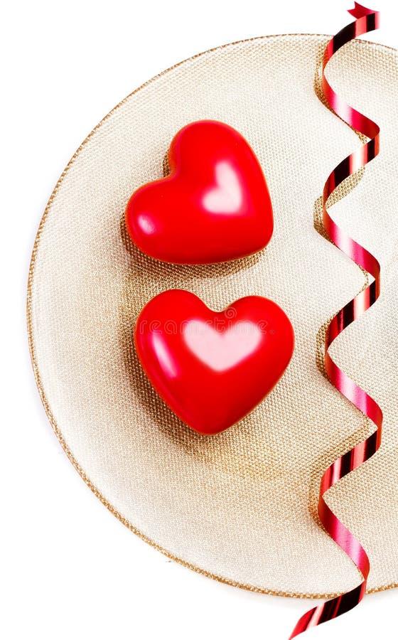 Dos corazones rojos grandes en una placa de oro aislada en blanco con el fest fotos de archivo libres de regalías