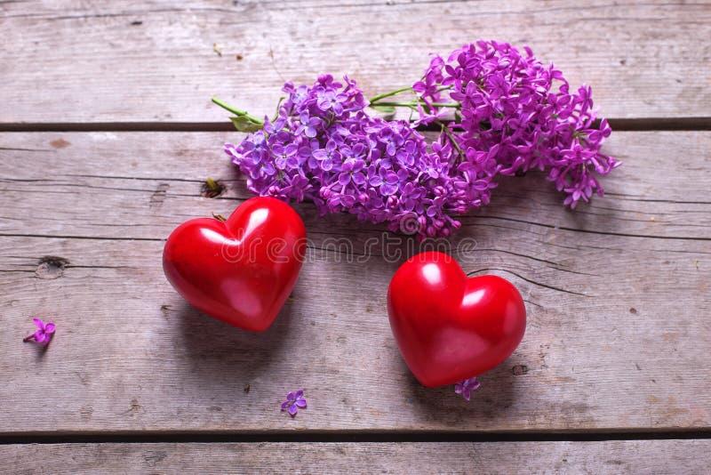 Dos corazones rojos y la lila violeta fresca florece en el pl de madera envejecido fotos de archivo libres de regalías
