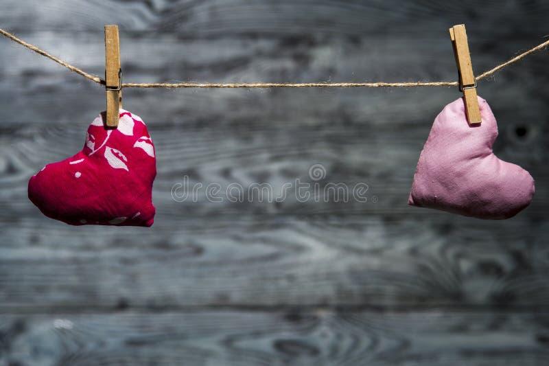 Dos corazones rosados aparte en fondo de madera imagenes de archivo
