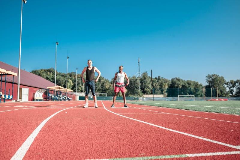 Dos corredores contra el cielo azul en el estadio calientan fotos de archivo libres de regalías