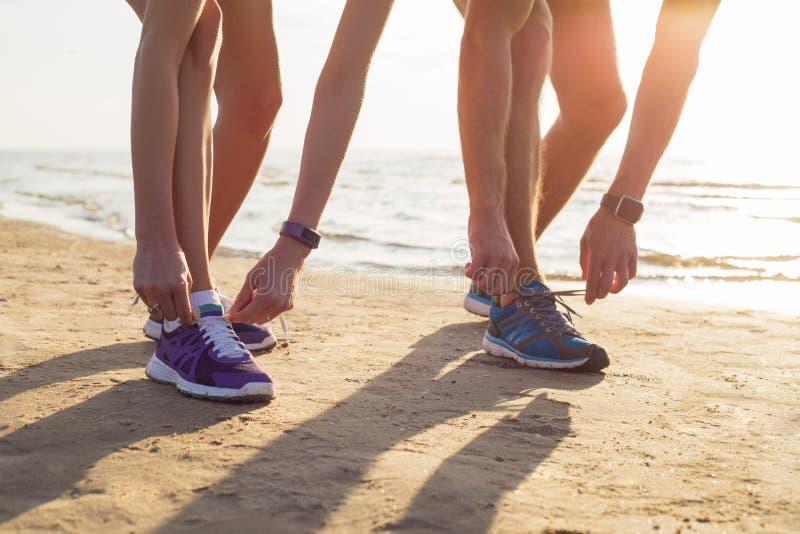 Dos corredores que atan sus zapatillas deportivas foto de archivo