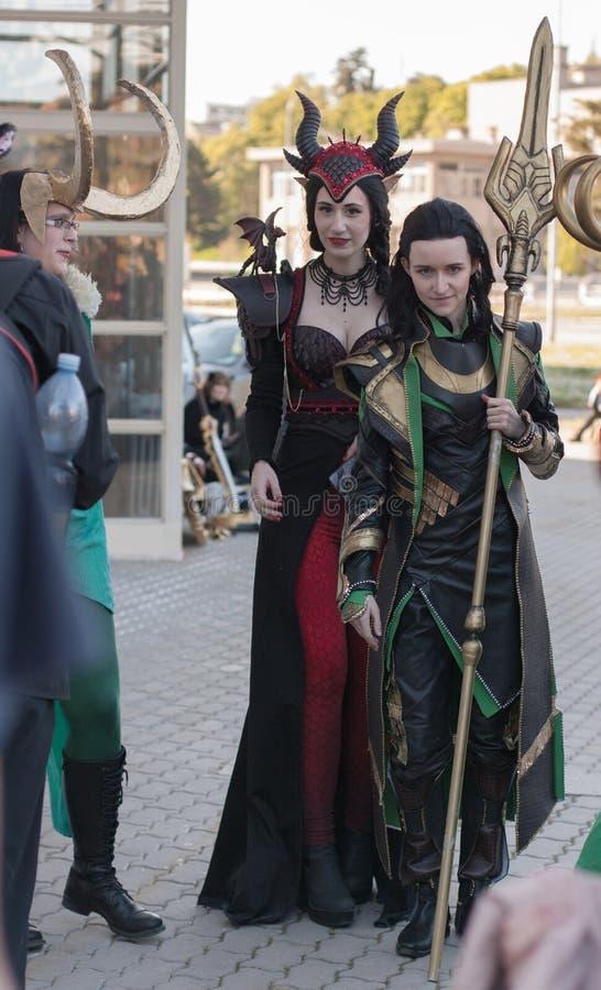 Dos cosplayers vestidos como los caracteres Ruby Dragon y Loki imagenes de archivo