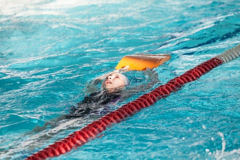 Dos crawlé de natation de sportif de jeune fille avec le kickboard dans la piscine images libres de droits