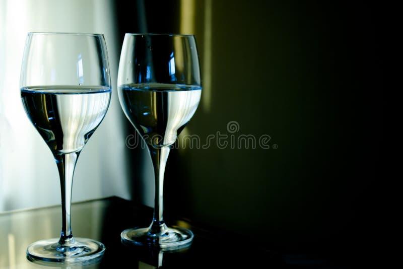 Dos cristales llenos de agua con el fondo verde imagen de archivo libre de regalías