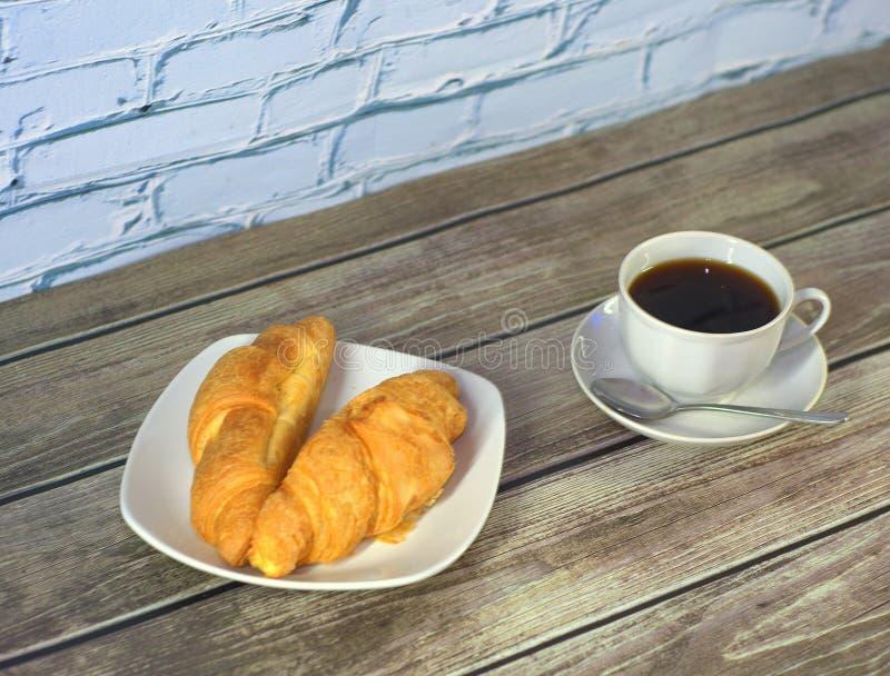 Dos cruasanes recientemente cocidos en una placa de cerámica blanca y una taza de café sólo en un platillo con una cuchara en una imagenes de archivo