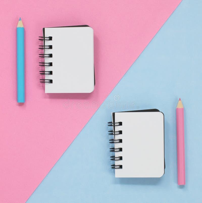 Dos cuadernos abiertos con los l?pices coloreados, en un rosa y un fondo diagonal azul foto de archivo