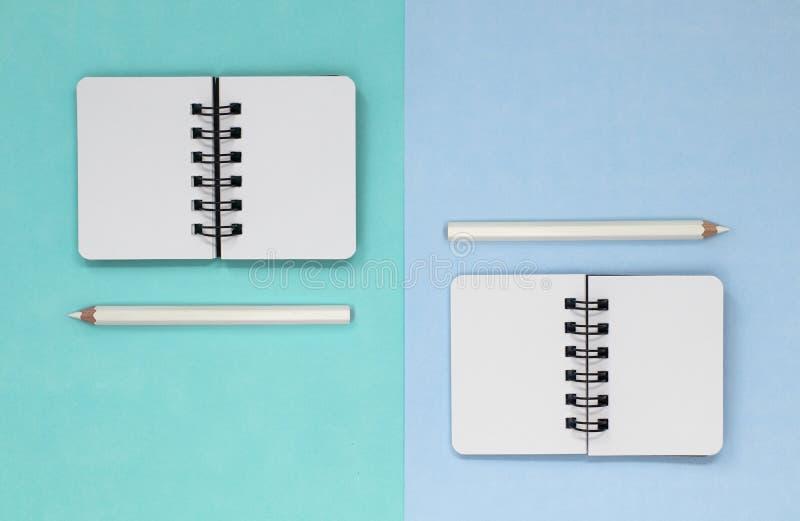 Dos cuadernos espirales abiertos y lápices blancos, en un fondo verde azul foto de archivo