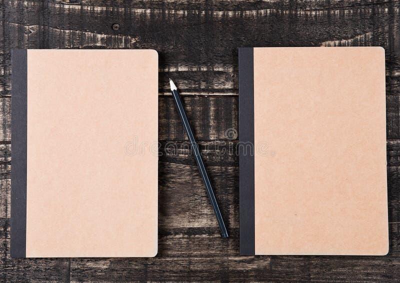 Dos cuadernos marrones en blanco con el lápiz negro fotografía de archivo libre de regalías