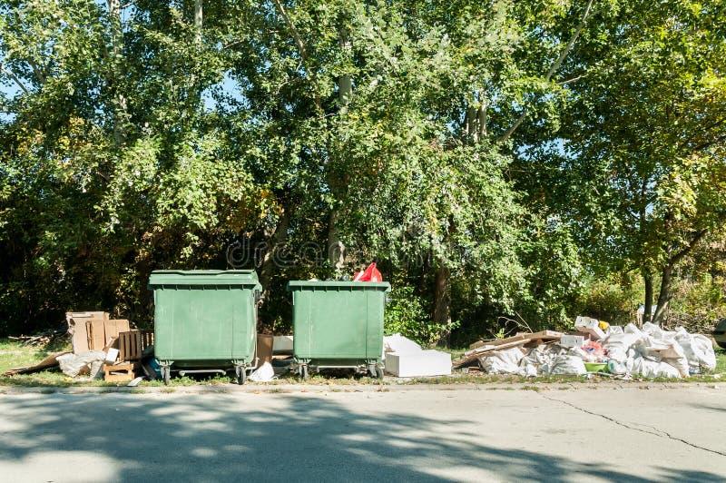 Dos cubos de la basura plásticos verdes grandes del contenedor por completo de litera del desbordamiento que contamina el parque  fotografía de archivo libre de regalías
