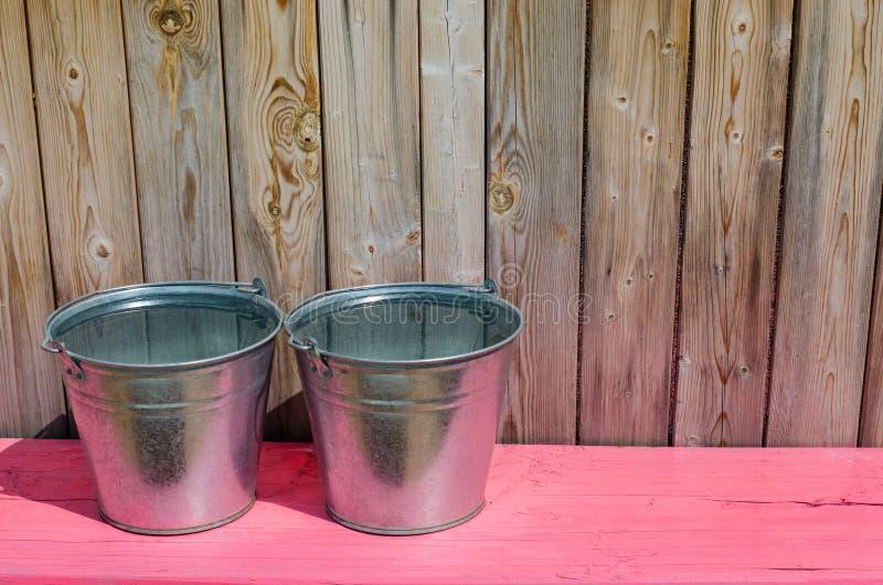 Dos cubos del metal de agua Banco de madera rosado Tabl?n de madera r?stico fotografía de archivo