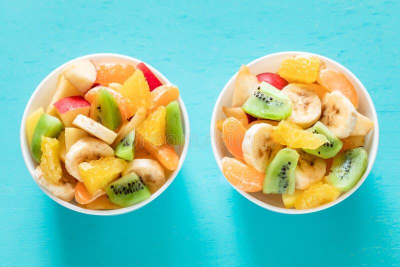 Dos cuencos blancos de ensalada de fruta fresca sana en fondo de la turquesa imagen de archivo libre de regalías