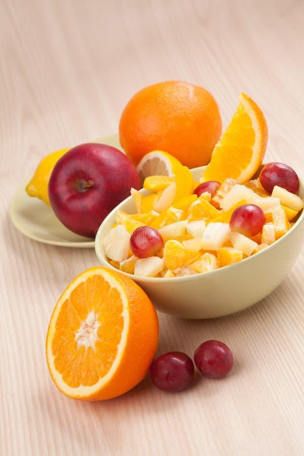 Dos cuencos con la ensalada de fruta en la tabla de madera con la mitad de la naranja imagen de archivo libre de regalías